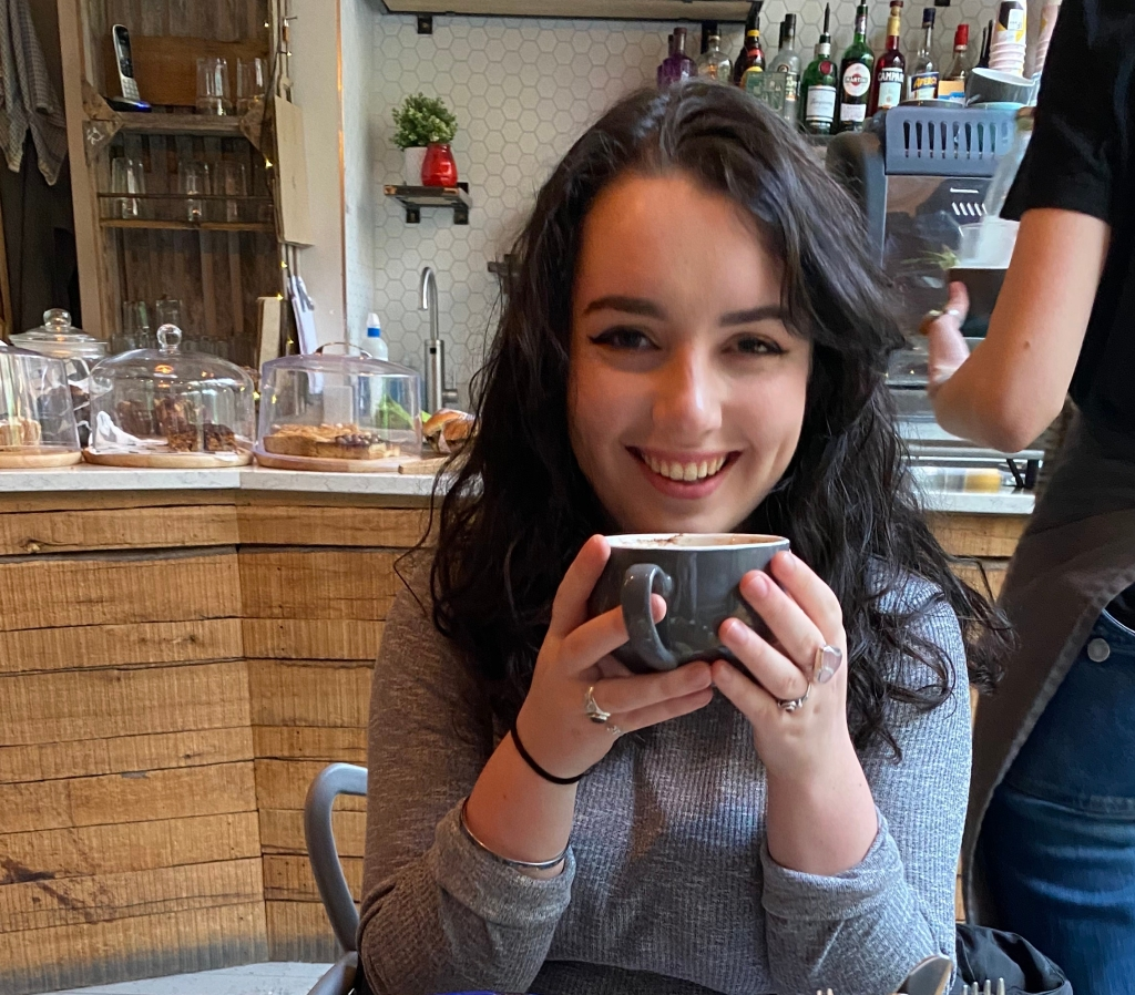 Georgie is sat in a coffee shop holding a mug near her face. In the background is the counter with some cakes sat on top.